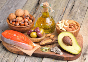 Image of healthy fats arrayed on a counter, like salmon and avocado