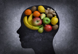 Image of fruits in the shape of a brain in a silhouette of a head