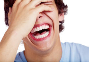 Image of young man enjoying the health benefits of a big laugh
